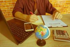 Chiuda su delle mani maschii sulla sua tastiera del ` s del calcolatore La seconda mano dentro sul touchpad Concetto del lavoro d Immagini Stock