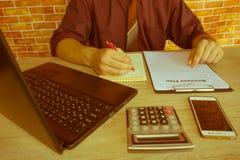 Chiuda su delle mani maschii sulla sua tastiera del ` s del calcolatore La seconda mano dentro sul touchpad Concetto del lavoro d Fotografia Stock Libera da Diritti