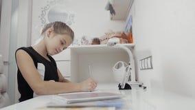 Chiuda su delle mani delle ragazze che scrivono sulla compressa alla sessione di compito Piccolo studente femminile a casa stock footage