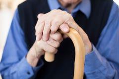 Chiuda su delle mani senior di Man's che tengono la canna di camminata fotografie stock libere da diritti