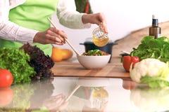 Chiuda su delle mani umane che cucinano l'insalata di verdure in cucina sulla tavola di vetro con la riflessione Pasto sano e Fotografia Stock