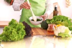 Chiuda su delle mani umane che cucinano l'insalata di verdure in cucina sulla tavola di vetro con la riflessione Pasto sano e Immagine Stock Libera da Diritti