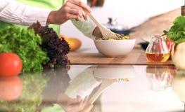 Chiuda su delle mani umane che cucinano l'insalata di verdure in cucina sulla tavola di vetro con la riflessione Pasto sano e Immagini Stock Libere da Diritti