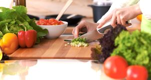 Chiuda su delle mani umane che cucinano l'insalata di verdure in cucina sulla tavola di vetro con la riflessione Pasto sano e Fotografia Stock Libera da Diritti