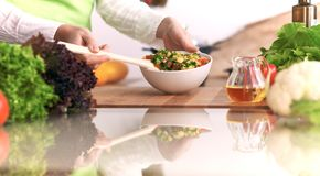 Chiuda su delle mani umane che cucinano l'insalata di verdure in cucina sulla tavola di vetro con la riflessione Pasto sano e Immagini Stock