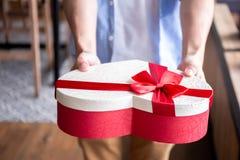 Chiuda su delle mani umane che ricevono un regalo attuale decorativo con Immagini Stock Libere da Diritti
