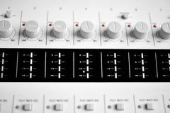 Chiuda su delle manopole di un tecnico del suono fotografia stock