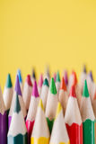 Chiuda su delle matite di colore con colore differente sopra fondo giallo Immagine Stock Libera da Diritti