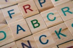 Chiuda su delle mattonelle di legno dell'alfabeto mettono a fuoco sulla lettera A B e C immagine stock libera da diritti