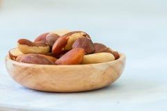 Chiuda su delle noci del Brasile in un piatto di legno Fotografia Stock