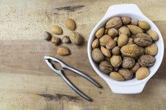 Chiuda su delle noci, delle nocciole e delle mandorle sulla tavola di legno Immagine Stock Libera da Diritti