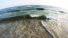 Chiuda su delle onde del mare sulla spiaggia un giorno di estate soleggiato stock footage
