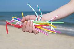 Chiuda su delle paglie di plastica della tenuta della mano che inquinano la spiaggia fotografia stock
