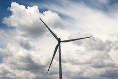 Chiuda su delle pale di una turbina di energia eolica contro le belle nuvole Fotografia Stock Libera da Diritti