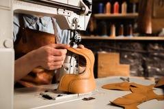 Chiuda su delle parti di cuoio di cucitura di un artigiano maschio Immagini Stock