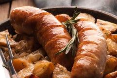Chiuda su delle patate e delle salsiccie arrostite in pentola con la forcella ed il coltello fotografia stock