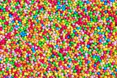 Chiuda su delle perle commestibili variopinte dello zucchero per la decorazione dell'alimento Fotografia Stock