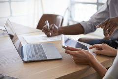 Chiuda su delle persone di affari che lavorano al computer portatile in sala del consiglio fotografia stock