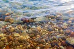 Chiuda su delle pietre colorate sotto l'acqua salata al coa del mar Morto Fotografia Stock