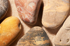 Chiuda su delle pietre del mare sulla sabbia Priorità bassa della spiaggia di estate Fotografie Stock