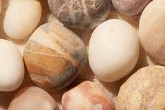 Chiuda su delle pietre del mare sulla sabbia Priorità bassa della spiaggia di estate Immagini Stock