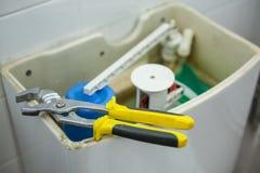 Chiuda su delle pinze che si trovano sulla toilette Immagini Stock