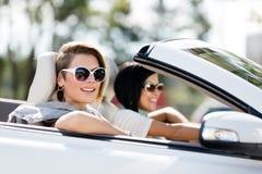 Chiuda su delle ragazze in occhiali da sole nell'auto fotografia stock