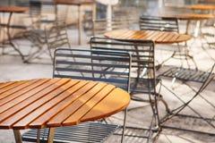 Chiuda su delle tavole e delle sedie di legno rotonde Fotografia Stock