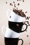 Chiuda su delle tazze bianche e nere sulla pila con la caduta chicchi di caffè arrostiti marrone Immagine Stock