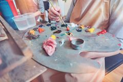 Chiuda su delle tonalità di miscelazione del pittore sulla tavolozza Immagine Stock