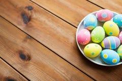 Chiuda su delle uova di Pasqua colorate sul piatto fotografie stock