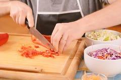 Chiuda su delle verdure di taglio dell'uomo sul bordo Fotografia Stock