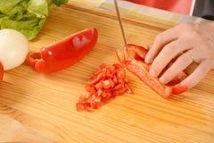 Chiuda su delle verdure di taglio dell'uomo sul bordo Immagine Stock