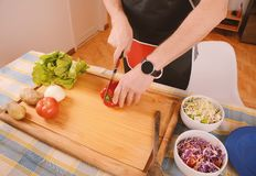 Chiuda su delle verdure di taglio dell'uomo sul bordo Fotografie Stock Libere da Diritti