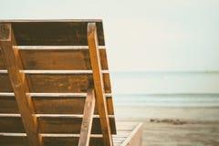 Chiuda su dello schienale di legno della sedia sulla spiaggia sabbiosa Fotografie Stock