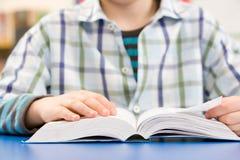 Chiuda in su dello scolaro che studia il manuale Immagini Stock Libere da Diritti