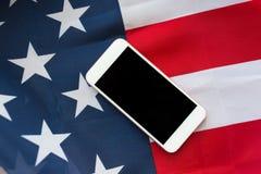 Chiuda su dello smartphone sulla bandiera americana Fotografie Stock Libere da Diritti