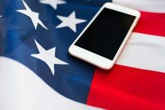 Chiuda su dello smartphone sulla bandiera americana Fotografie Stock