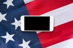 Chiuda su dello smartphone sulla bandiera americana Fotografia Stock