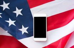 Chiuda su dello smartphone sulla bandiera americana Immagine Stock Libera da Diritti