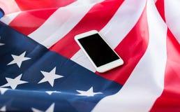 Chiuda su dello smartphone sulla bandiera americana Immagine Stock