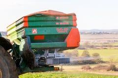 Chiuda su dello spalmatore del fertilizzante e del trattore nel campo Immagini Stock