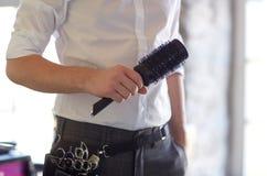 Chiuda su dello stilista maschio con la spazzola al salone Fotografie Stock Libere da Diritti