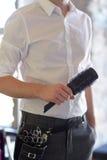 Chiuda su dello stilista maschio con la spazzola al salone fotografie stock