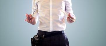 Chiuda su dello stilista maschio con le forbici al salone immagine stock