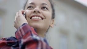 Chiuda su dello studente afroamericano che ha conversazione sul telefono nella città stock footage