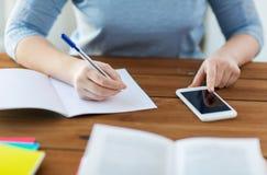 Chiuda su dello studente con lo smartphone ed il taccuino Immagini Stock Libere da Diritti