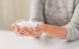 Chiuda su dello zucchero di grumo bianco in mani della donna fotografia stock