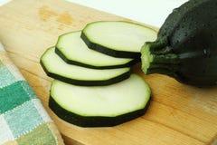 Chiuda su dello zucchini affettato sul tagliere di legno Immagine Stock
