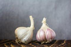Chiuda su di aglio crudo sul tagliere di legno su fondo grigio, horisontal fotografia stock
